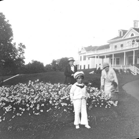 Two women and two children near flowerbeds in front of a very posh residence.