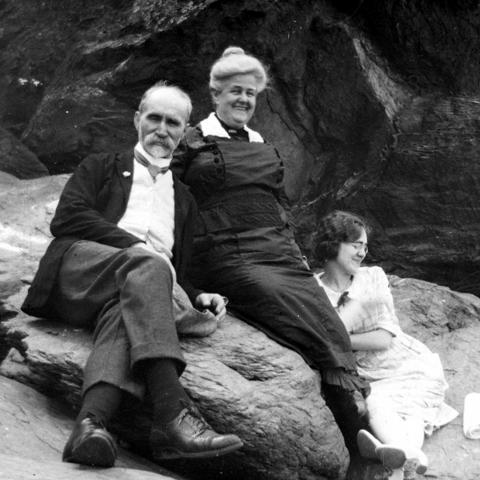 A rather distinguished older couple and a young woman sitting on a rock, relaxed and smiling.