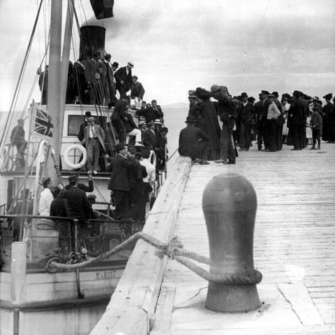 Dozens of passengers aboard a steamboat, with many others waiting to board.