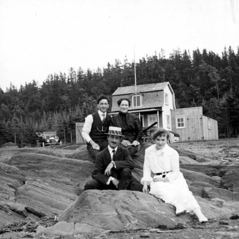 Des membres d'une famille sont assis sur des roches devant un chalet.