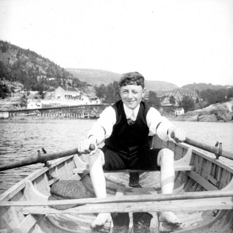 A young man sitting in a rowboat.