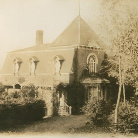 Résidence ancienne entourée de verdure et à l'architecture élaborée.