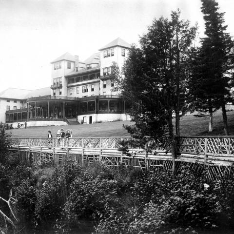 A large hotel with big verandas, ladies and young childrentaking in the scenery near a fence.