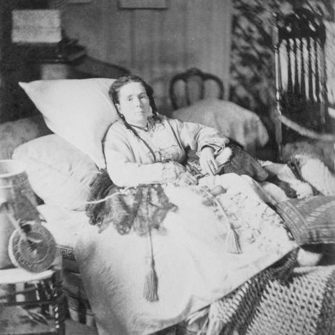 Photographie en noir et blanc d'une femme malade qui se repose dans un lit très confortable.