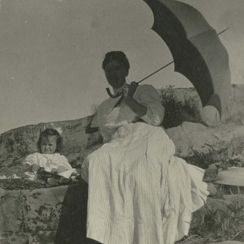 A women in a long dress and a young child sitting on a rock, with a parasol protecting them from the sun.