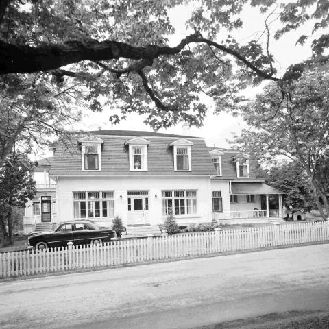A white house with a mansard roof near a dirt road, with an automobile parked out front.