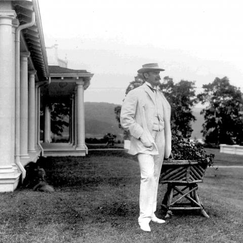 An elegant man wearing white and posing near an impressive residence, with a dog lying beside the house.