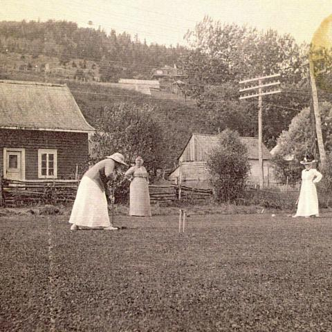 Three women play croquet near houses at the foot of a mountain.