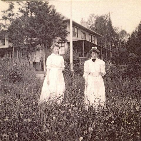 Two young women in dresses posing in a field near a house, each holding a white container.