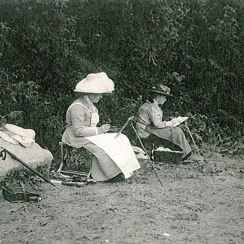 Two women painting on a beach, canvases on portable easels.