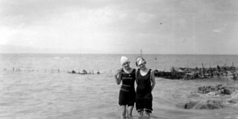 Deux jeunes femmes en maillot de laine se tiennent côte-à-côte, les pieds dans le fleuve. Une pêche à fascine se trouve en arriè