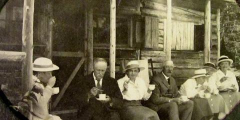 Sept adultes bien mis prennent le thé, assis sur la galerie rudimentaire d'un chalet de bois rond.