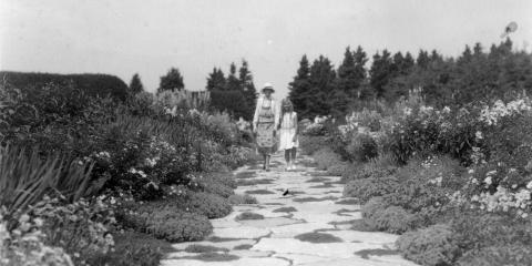 Une femme en tablier et une jeune fille marchent dans une l'allée fleurie d'un grand jardin.